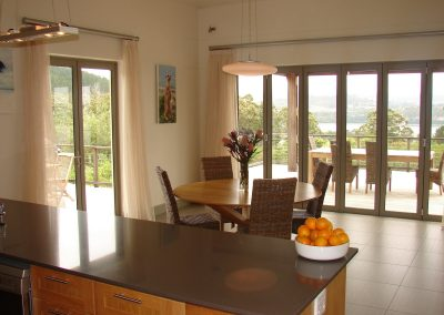 View from kitchen through dining area to outside deck which faces the lagoon